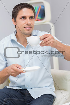 Thoughtful young man drinking tea at home