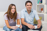 Cute couple sitting on sofa with tea cups at home