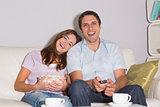 Cheerful couple watching TV with popcorn bowl on sofa at home