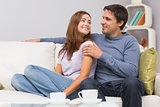 Loving couple looking at each other on sofa at home
