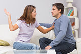 Young woman about to slap man in the living room at home