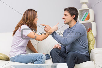 Angry couple having an argument in their living room