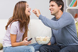 Cheerful man feeding popcorn to woman on sofa