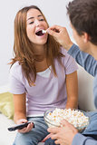 Cropped man feeding popcorn to a happy woman at home