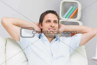 Thoughtful man sitting with hands behind head in the living room