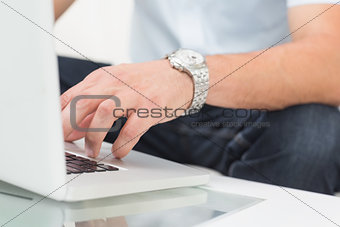 Mid section of a man using laptop on coffee table