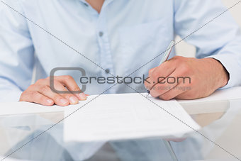 Close-up mid section of a man writing documents