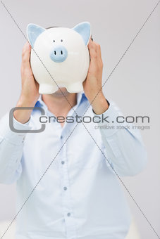Casual man holding piggy bank in front of his face