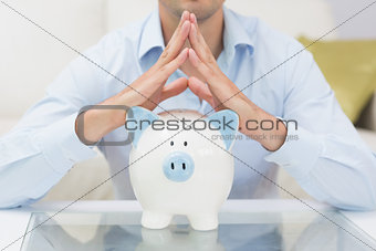 Mid section casual man with piggy bank in living room