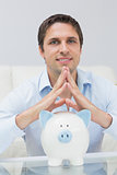Handsome casual man with piggy bank in living room