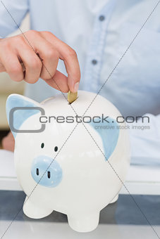 Close-up mid section of a man putting coin into piggy bank