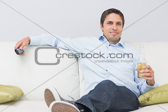 Relaxed man with a drink and remote control sitting on sofa at home