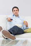 Man with a drink and remote control sitting on sofa
