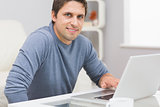 Portrait of smiling man using laptop in living room