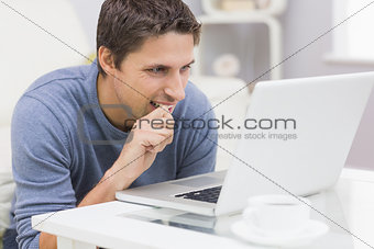 Thoughtful young man using laptop in living room