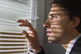 Serious businessman peeking through blinds in office