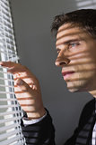 Serious young businessman peeking through blinds in office