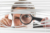 Businessman peeking through blinds with magnifying glass