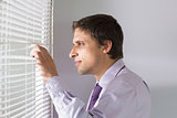 Businessman peeking through blinds in office