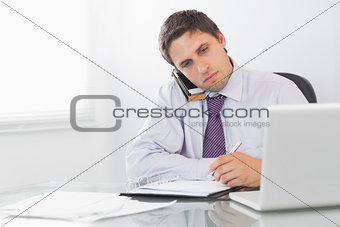 Businessman on call while writing in diary at office