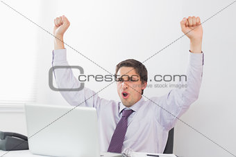 Businessman cheering in front of laptop in office
