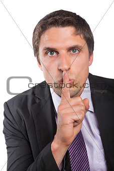 Green eyed businessman with finger to his lips
