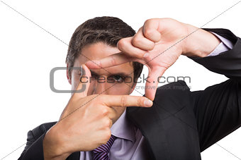 Close-up of a businessman looking through finger frame