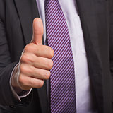 Businessman in suit gesturing thumbs up