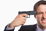 Close-up of a businessman holding a gun to head
