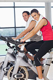 Young woman and man working out at spinning class