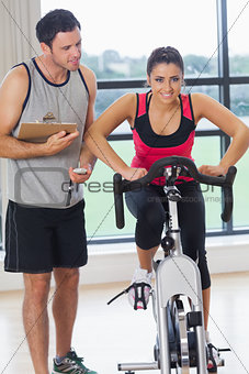 Trainer watching woman work out at spinning class