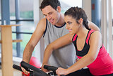 Trainer helping woman work out at spinning class