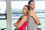 Serious woman and man standing back to back in gym