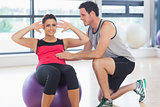Trainer helping woman do abdominal crunches  on fitness ball