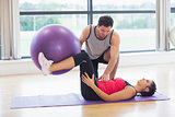 Trainer helping young woman with fitness ball at gym