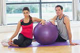 Young woman and man with fitness ball sitting at gym