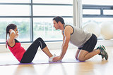 Trainer helping woman do abdominal crunches in gym