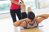 Female trainer assisting man with his exercises in gym