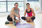 Woman and man with water bottles sitting at gym