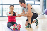 Male trainer assisting woman with pilate exercises in fitness studio