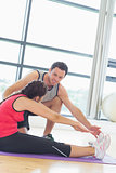 Trainer assisting woman with pilate exercises in fitness studio