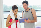 Fit couple looking at digital table in exercise room