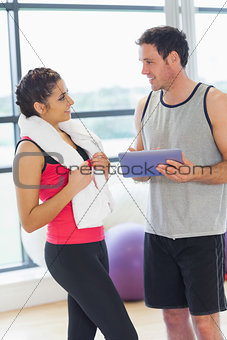 Fit couple with at digital table in exercise room