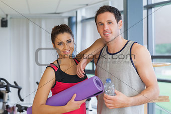 Fit couple with water bottle and exercise mat in exercise room