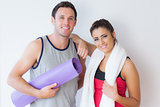 Portrait of a fit young couple with towel and exercise mat