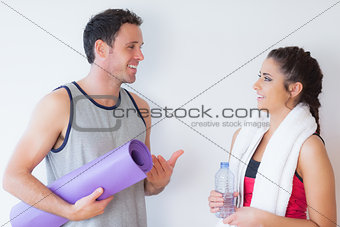 Fit young couple with towel and exercise mat chatting