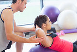 Male trainer helping woman do crunches  on fitness ball at gym