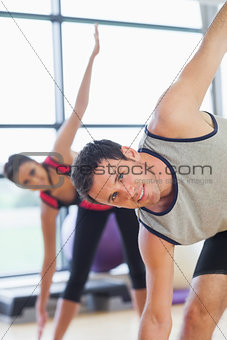 Two sporty people stretching hands at yoga class