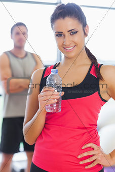 Fit woman holding water bottle with friend in background in exercise room