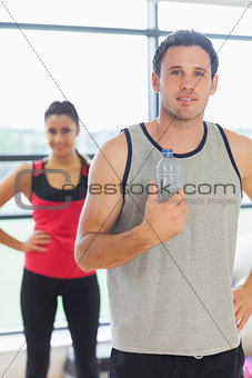 Fit man holding water bottle with friend in background in exercise room